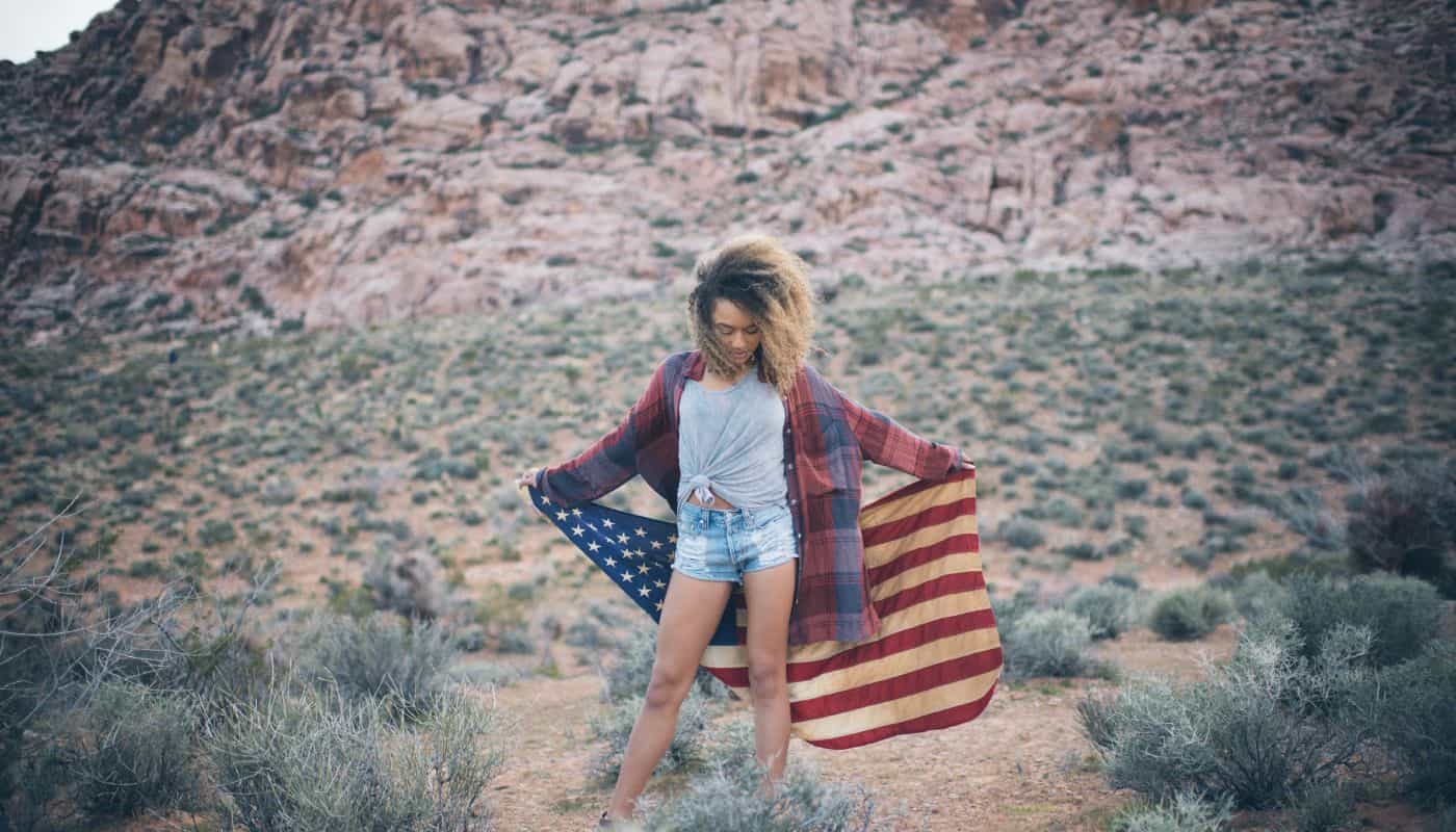 A young Black woman with natural hair holds and American flag in the desert during a digital photography session with Spanki Mills