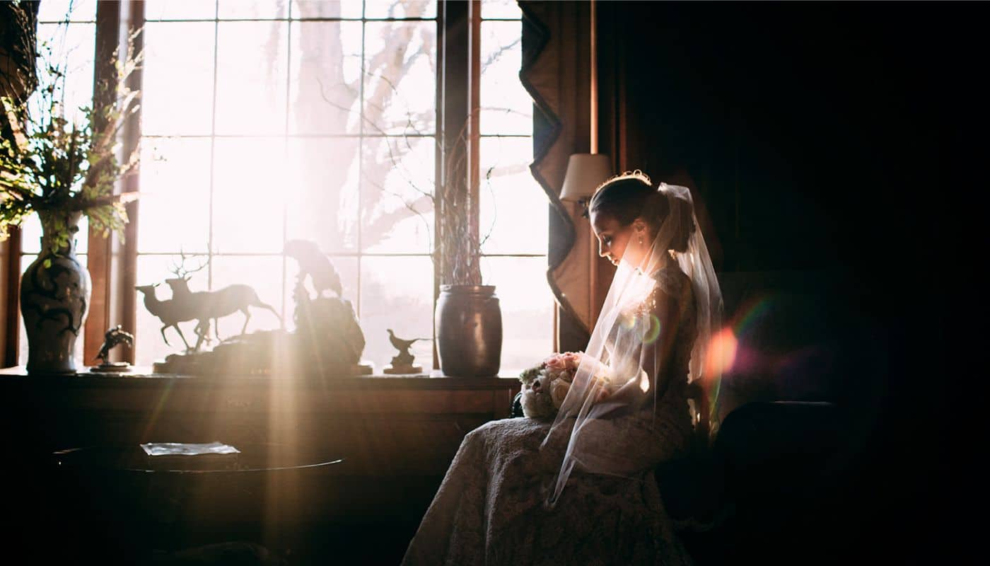 A bride in a long veil is backlit by the sun streaming through a large window in this wedding photo shot by photographer Ginny Corbett