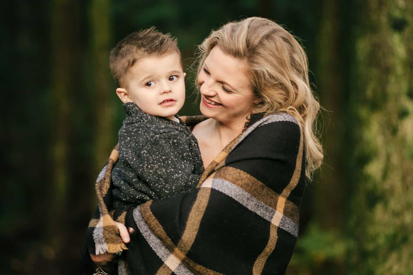 A mom holds her young son while wrapped in a wool blanket.