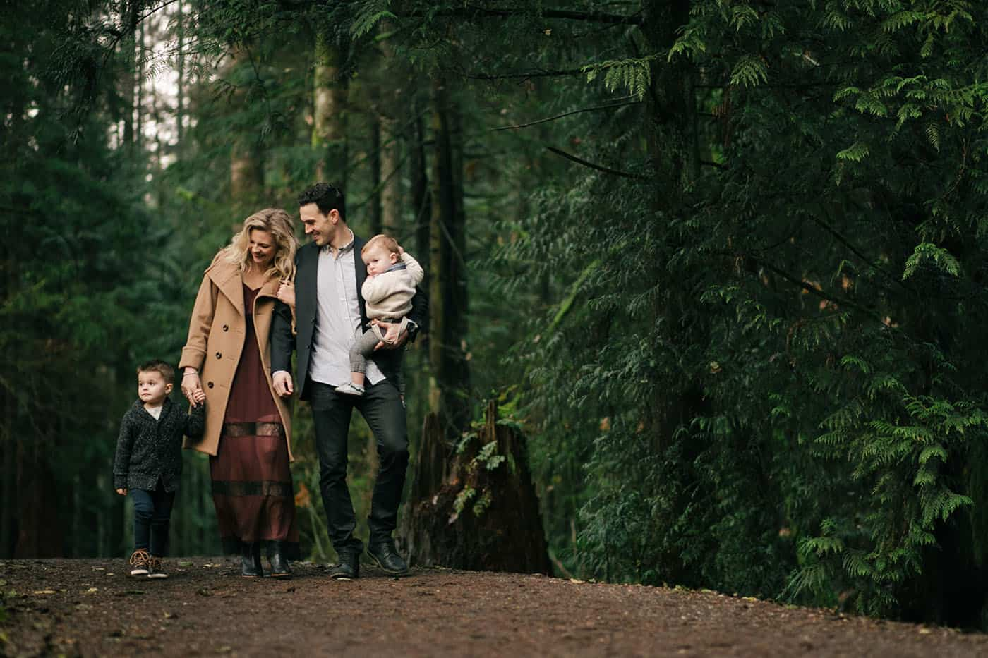 A husband and wife stroll through the woods with their two young sons in one of our favorite family portrait poses.