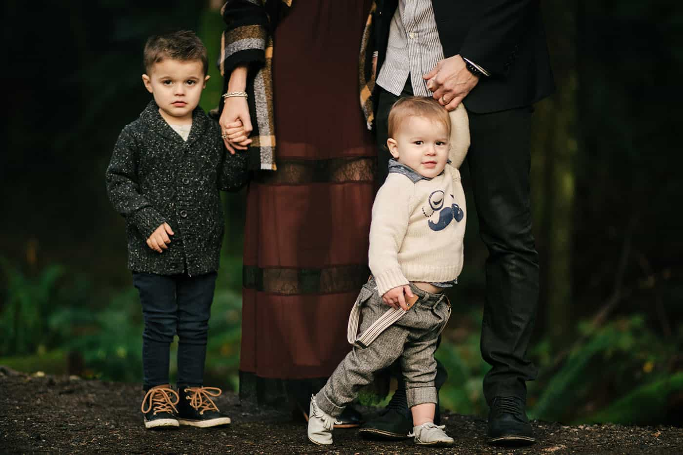 Parents are photographed from the waist-down, holding hands with their two toddler sons who are seen full-length in their fall outfits.