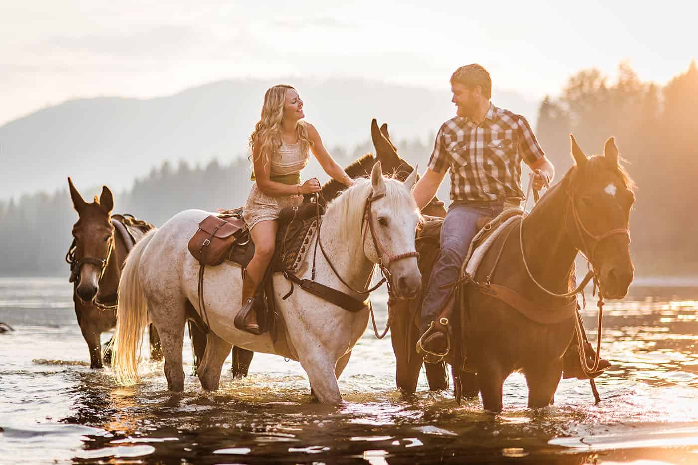 Epic Montana Photo Locations - beautiful couple on horseback in a river at sunset