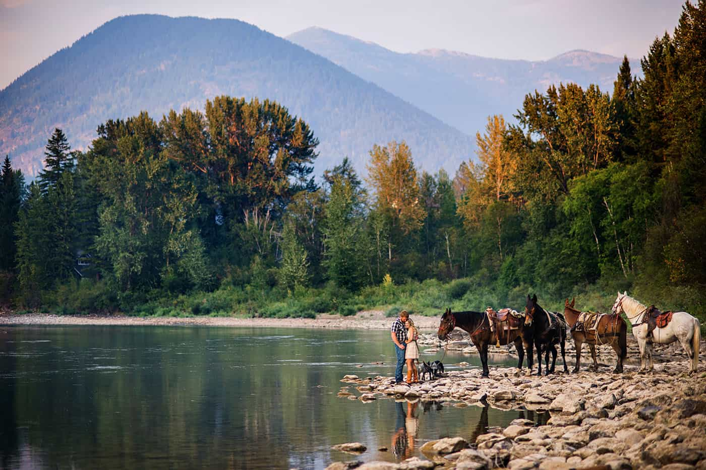 Epic Montana Photo Locations - beautiful couple with horses by a river at sunset