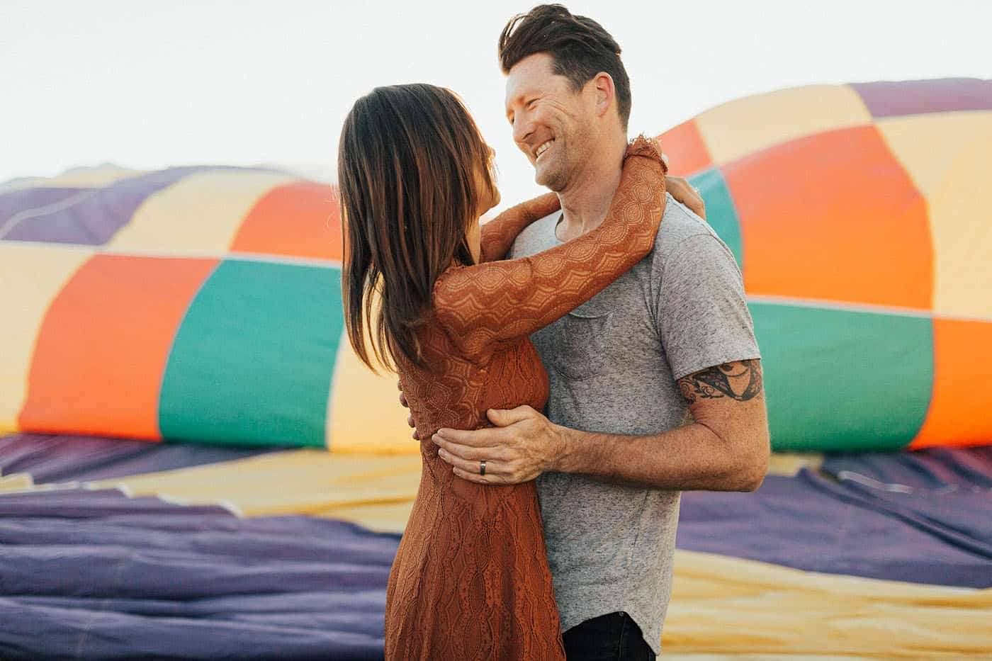 Memorable Photo Locations - tattooed couple hugging at a hot air balloon festival