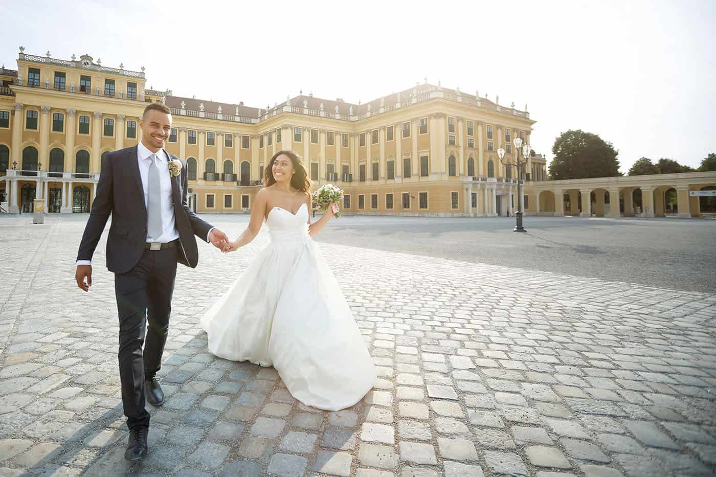 This is the Key to Amazing Client Relationships | A bride and groom stroll through a massive stone courtyard as the sun pours over them.