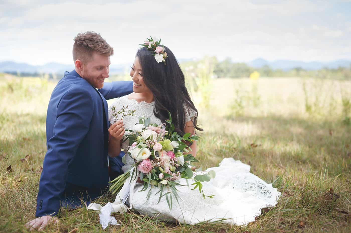 A bride and groom sit together in a field full of wildflowers.