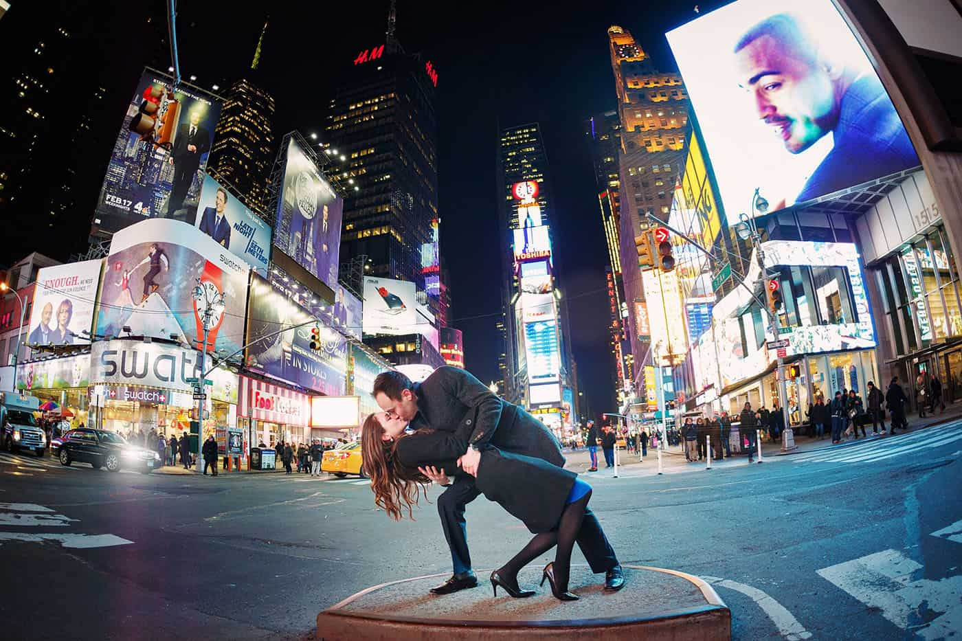 This is the Key to Amazing Client Relationships | A man dips and kisses his partner in a major Times Square intersection at nighttime.