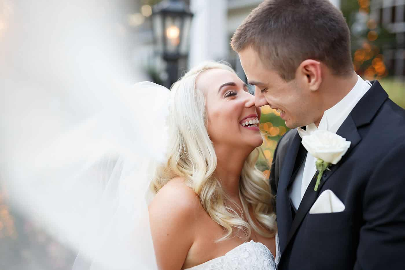 This is the Key to Amazing Client Relationships | A bride and groom move in to kiss as the bride's veil flies toward the camera lens.