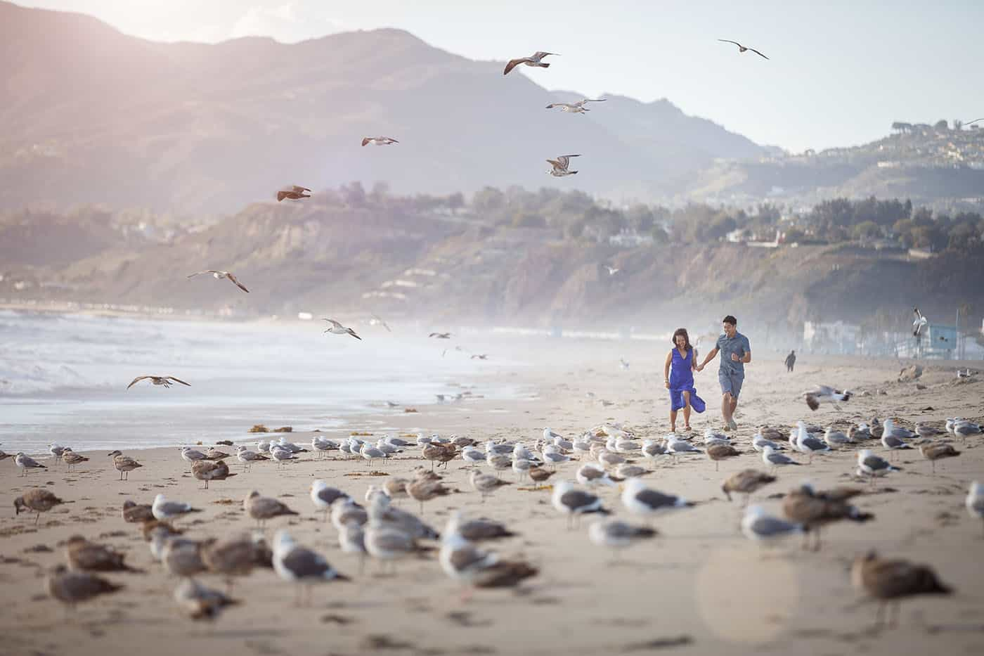 This is the Key to Amazing Client Relationships | A newly engaged couple runs along the shore of a seagull-nested beach.