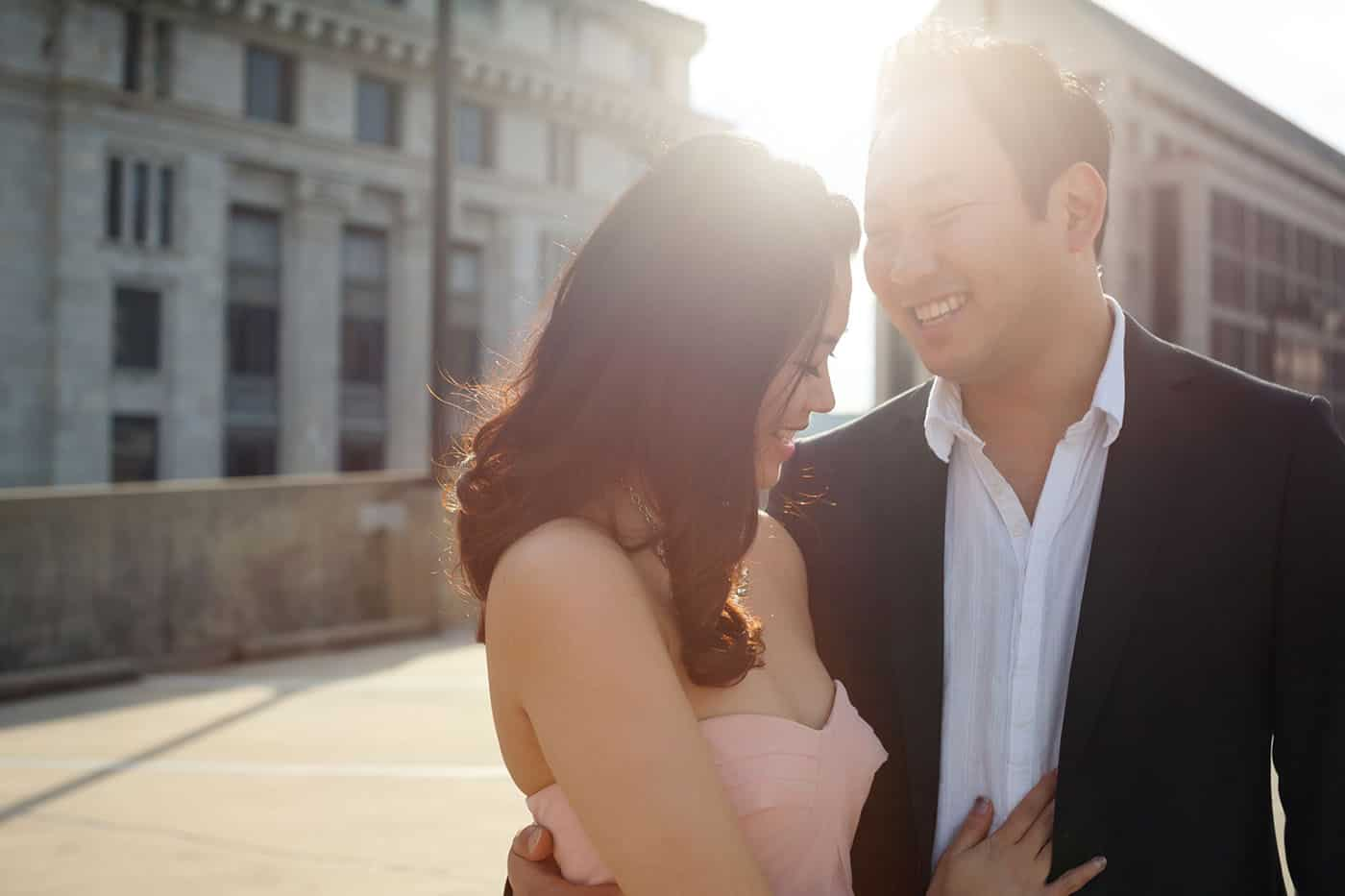 This is the Key to Amazing Client Relationships | An engaged couple leans in toward one another as a flare of sun glows behind them.