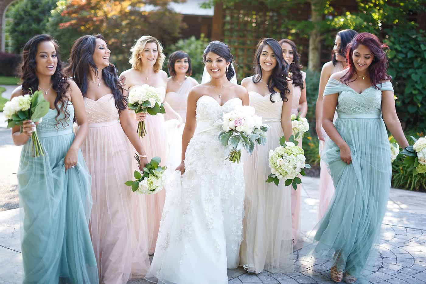 This is the Key to Amazing Client Relationships | A group of pastel-gowned bridesmaids stroll outside alongside the bride.