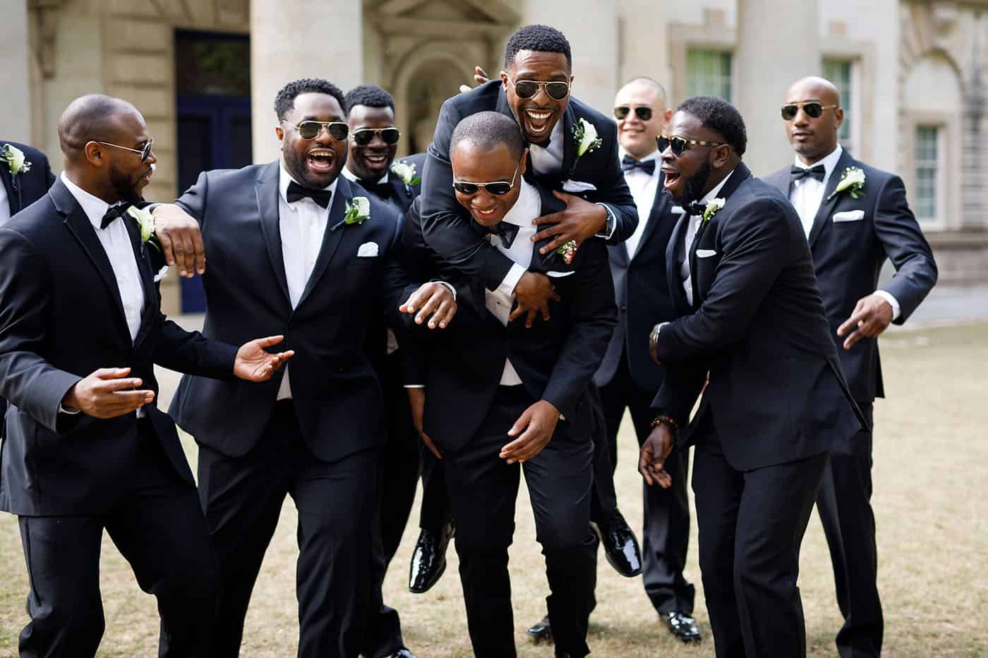 This is the Key to Amazing Client Relationships | A throng of groomsmen in black tuxes horseplay in the courtyard of a beautiful hotel.
