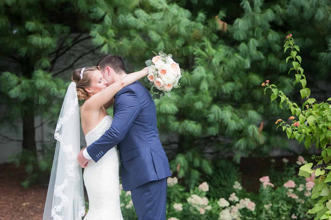 bride and groom hugging with bouquet by customer service whiz cinnamon wolfe