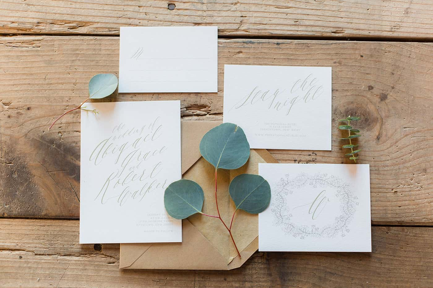 wedding invitation set on a wooden table with leaves by customer service whiz cinnamon wolfe