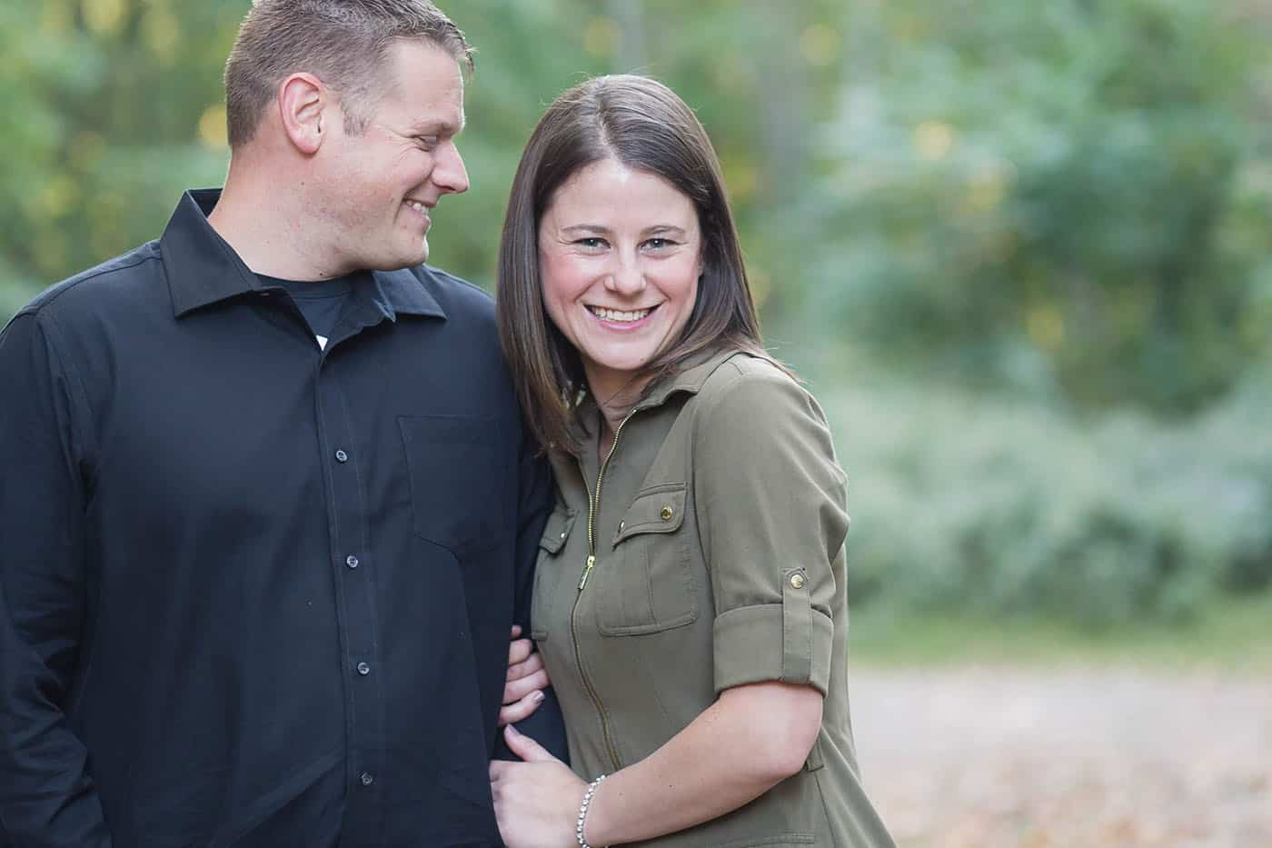outdoor engagement portrait in navy and olive by customer service whiz cinnamon wolfe