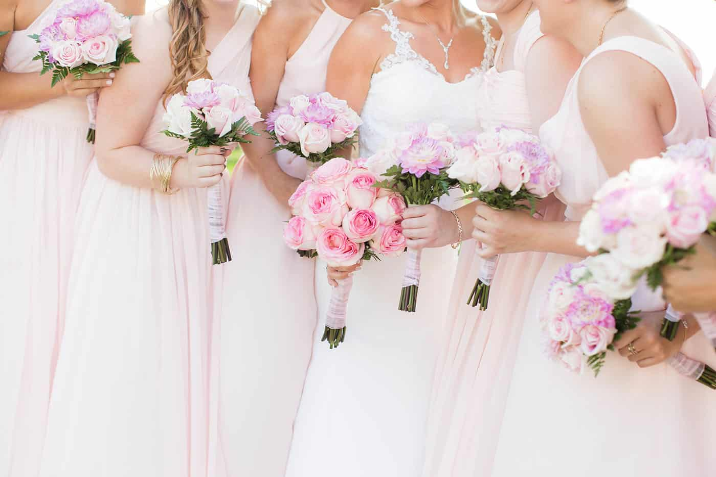 bridesmaids in pink dresses holding pink and purpose rose bouquets by customer service whiz cinnamon wolfe