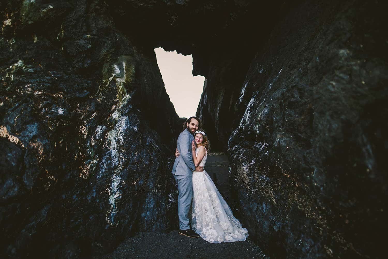 Color full-length portrait of a caucasion bride and groom embracing at the entrace to a sea cave. The groom has a brown beard and is wearing a gray suit, and the bride is wearing a flower crown over her blonde curls.