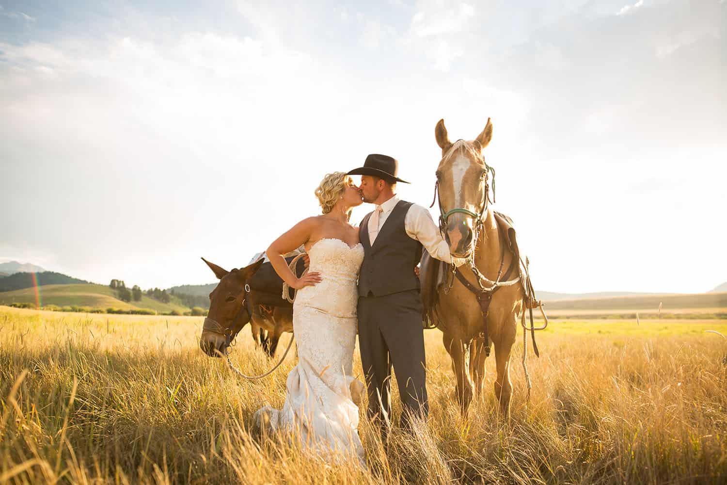 Color photo of a blonde bride kissing her cowboy-hatted groom in a field at midday. The two stand with their horses.