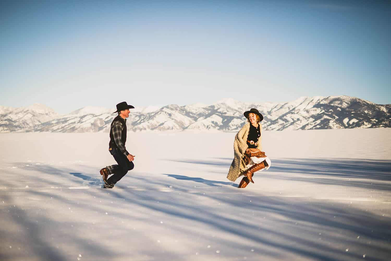 Color image of a caucasion couple in boots and cowboy hats tromping through a snowy landscape in the late afternoon.