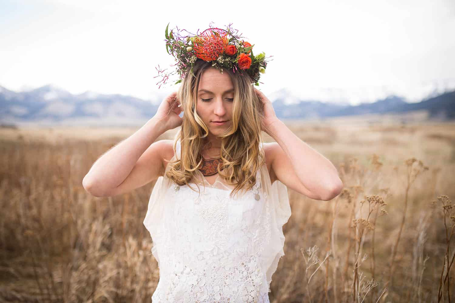 Color half-length photograph of a blonde bride wearing white overalls, a veil, and a flower crown, standing in open shade in a large overgrown field with mountains in the background.
