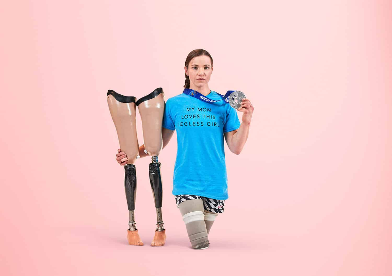 "Paralympic gold medalist Oksana Masters stands beside her prosthetics on a pink background showing off her silver medal and wearing a tee-shirt that says ""My Mom Loves This Legless Girl."""