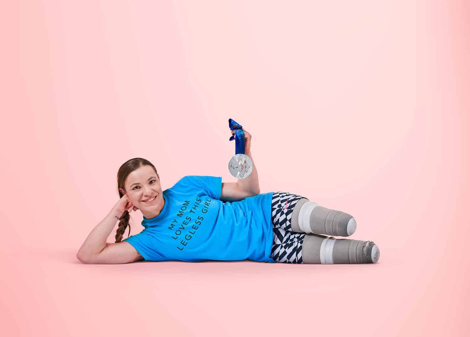 "Paralympic gold medalist Oksana Masters reclines without her prosthetics on a pink background showing off her silver medal and wearing a tee-shirt that says ""My Mom Loves This Legless Girl."""