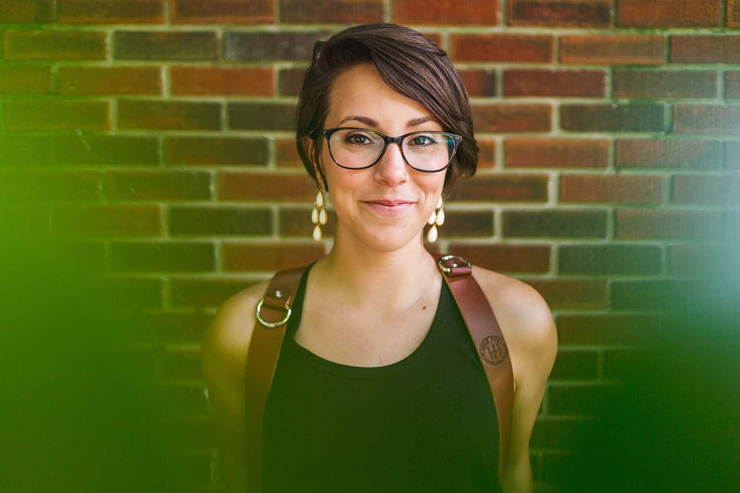 Photographer Mallory Regan, a caucasion woman with short brunette hair, glasses, and gold earrings, stands against a brick backdrop framed by leaves. She is smiling and wearing a HoldFast harness, made for carrying multiple cameras.
