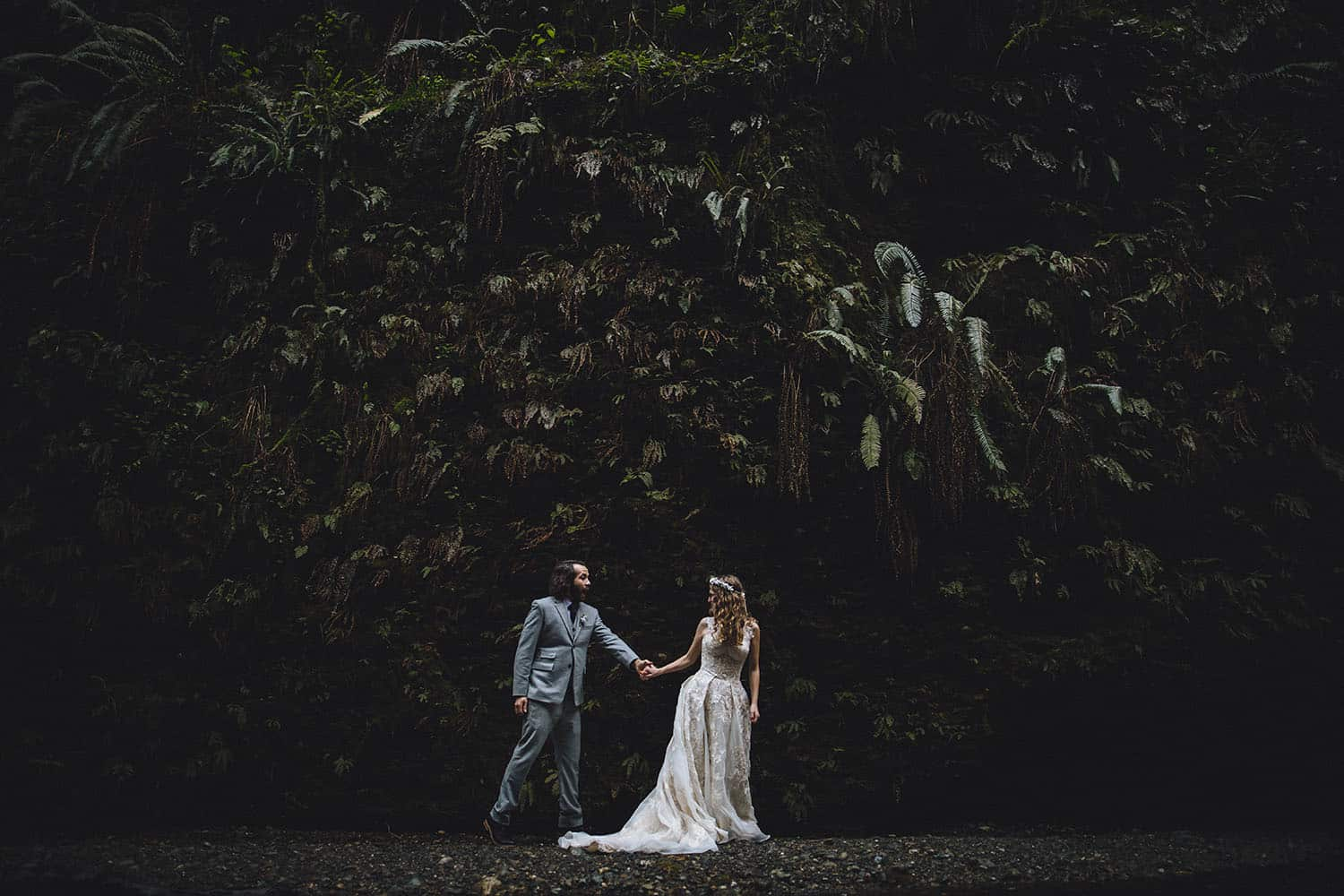 A bride leads her groom by the hand past a cliffside covered in ferns.