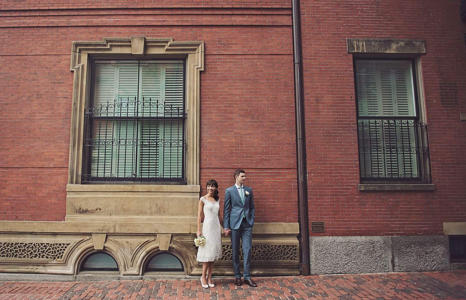 Bride and groom clasp hands in front of a tall brick wall. By Harris & Co.