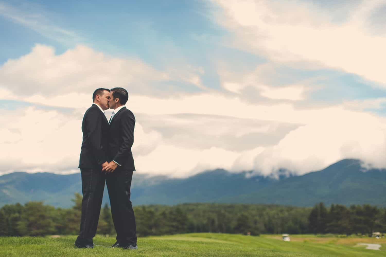 Two grooms kissing in an open field. By Harris & Co.