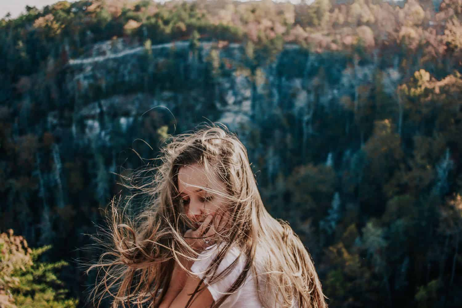 """Drop the Obsession with """"Pretty"""" Portrait Photography: Windblown woman stands on a mountainside, photographed by Crystal Anne Photography."""