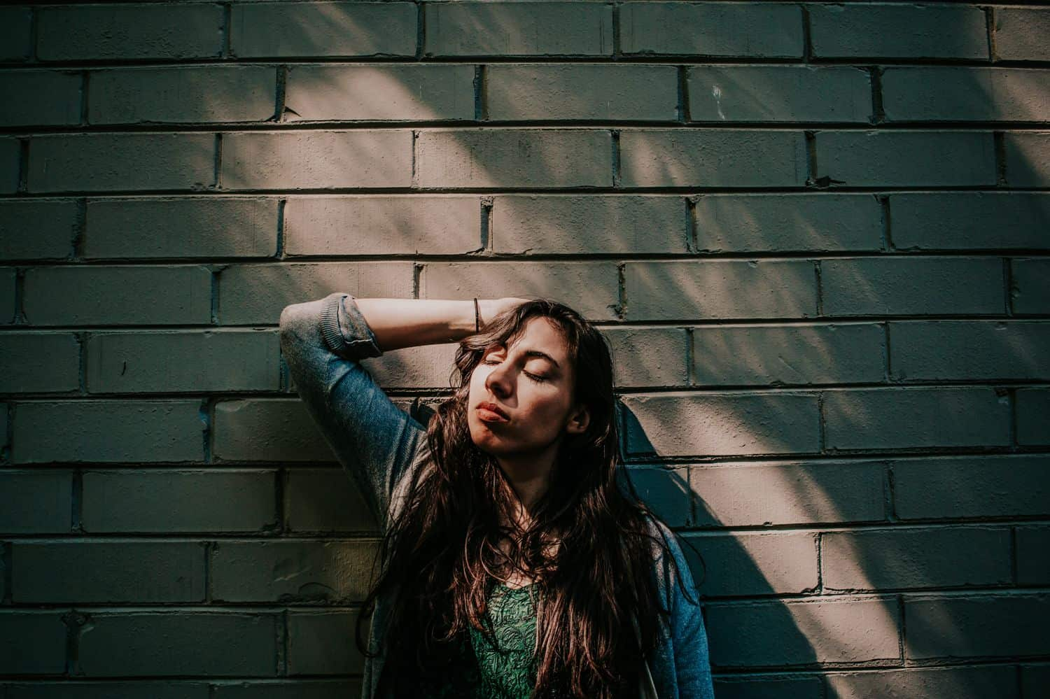 """Drop the Obsession with """"Pretty"""" Portrait Photography: Woman reclines back against a sand-colored brick wall, one hand behind her head, a streak of sunlight illuminating her face. Photographed by Crystal Anne Photography."""