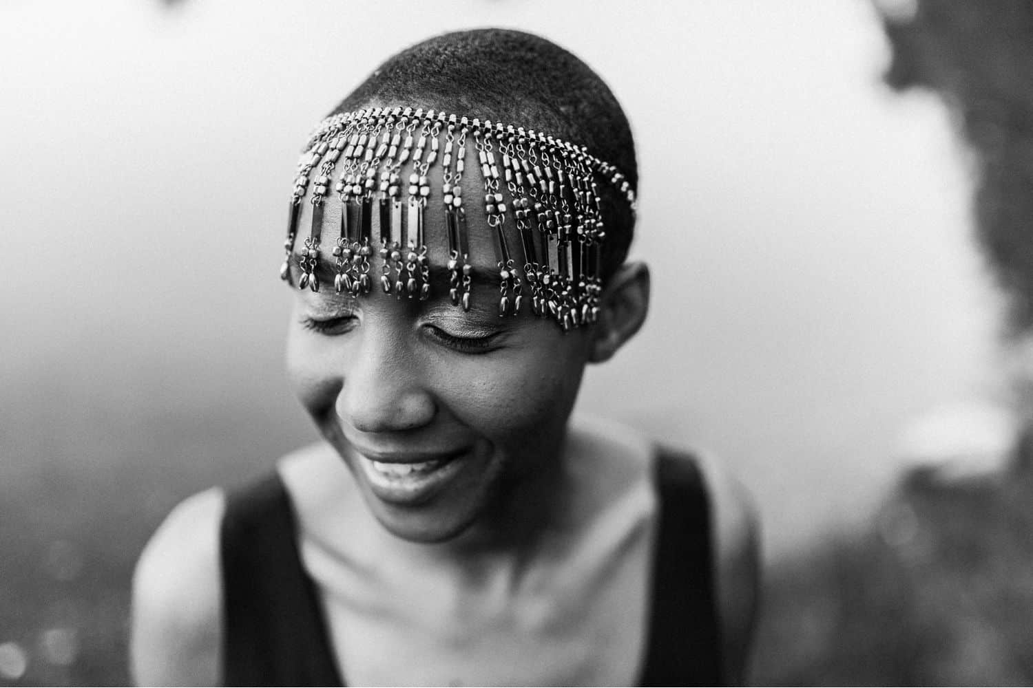 """Drop the Obsession with """"Pretty"""" Portrait Photography: Monochrome portrait of elegant Black woman photographed close-up with her eyes gently closed and a smile on her face. She wears a beaded headpiece and stands before a quiet pond. Photographed by Mae B."""