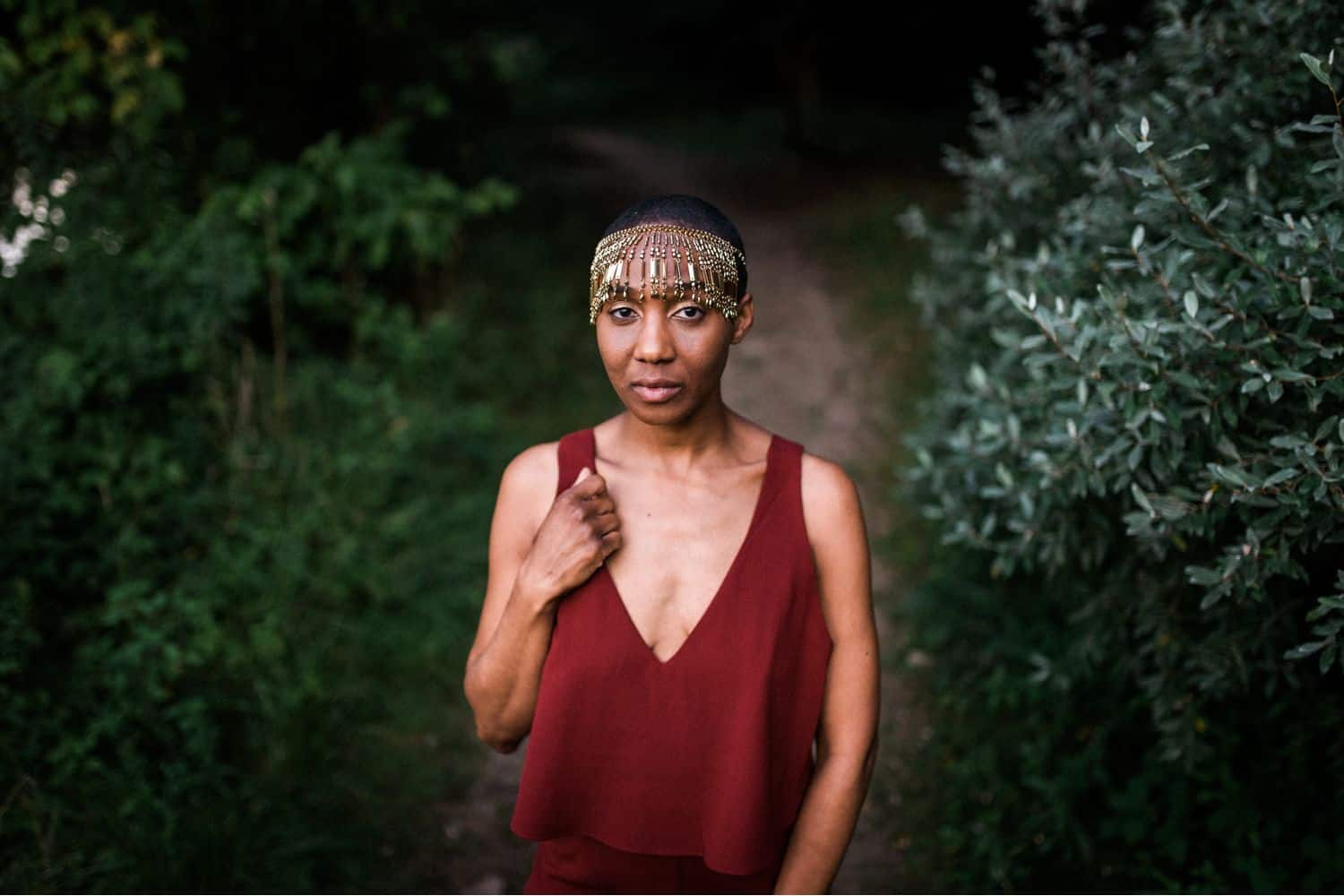 """Drop the Obsession with """"Pretty"""" Portrait Photography: A woman stands in a wooded pathway wearing a maroon linen blouse and a gold beaded headpiece. Photographed by Mae B."""