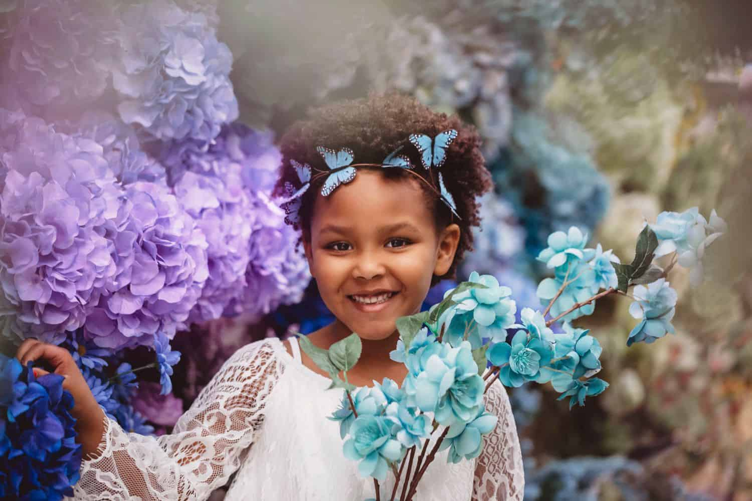 Portrait photography of little girl among silk flowers in a Michael's Craft Store for a photo project.
