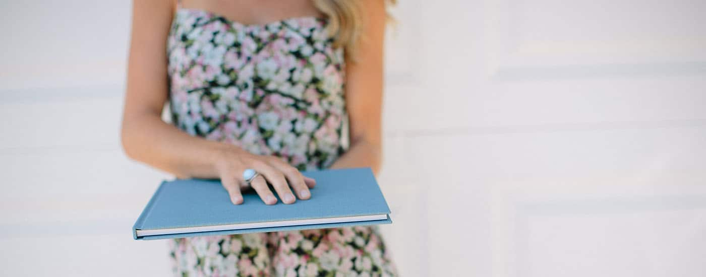 You Think You Want A Logo. What You Need Is A Legacy. - kiss book held by woman in a floral dress