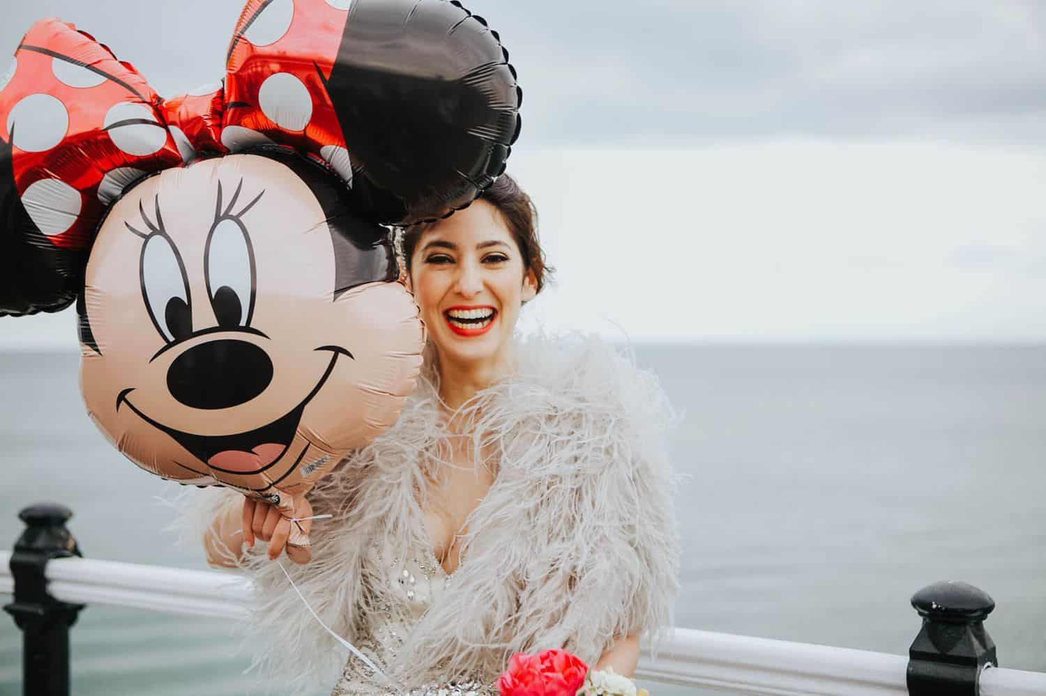How To Make A Photography Website Your Dream Clients Can't Resist: a bride draped in feathers holds a Minnie Mouse balloon in front of an expansive ocean scene.