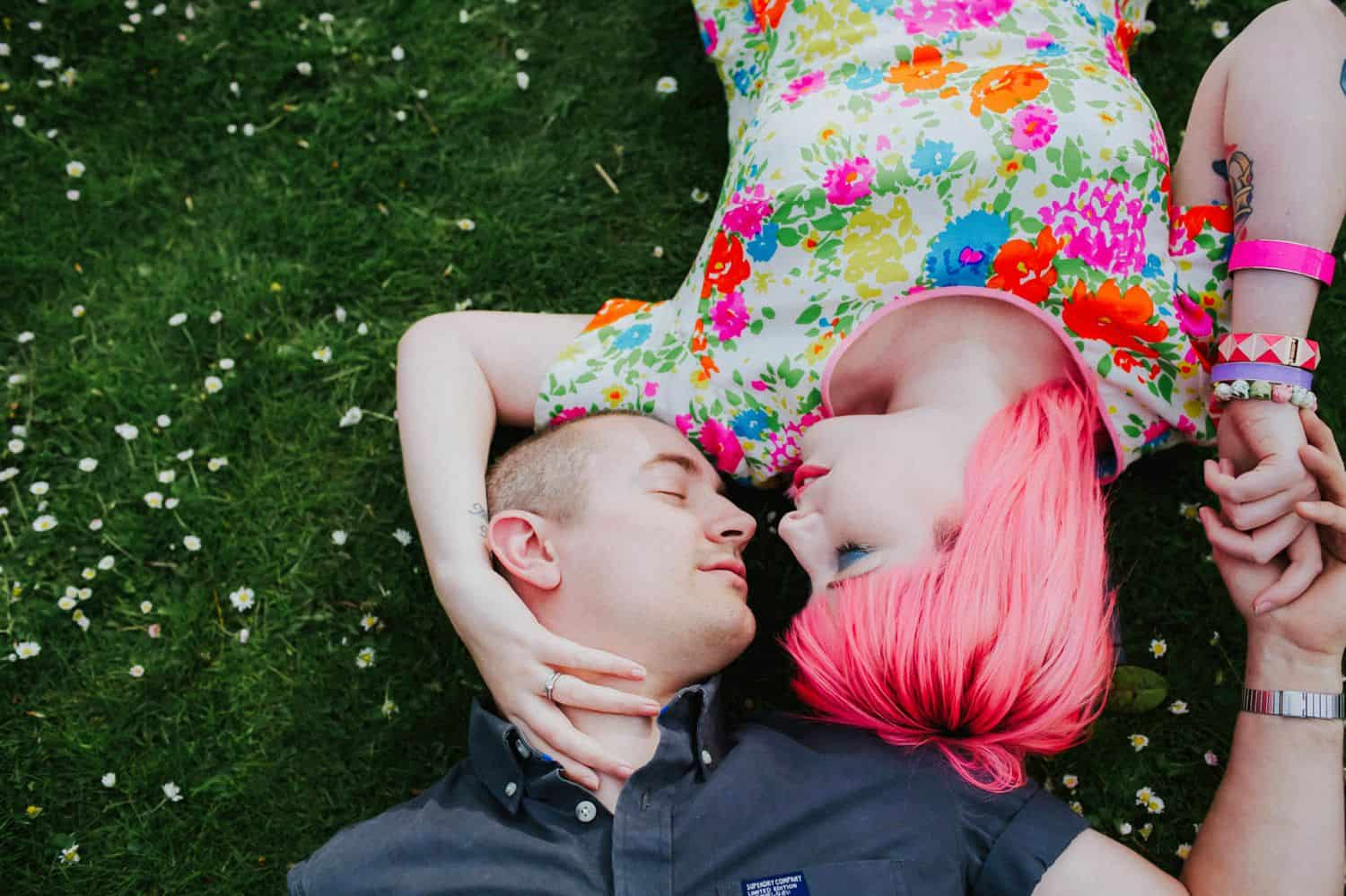 How To Make A Photography Website Your Dream Clients Can't Resist: A pink-haired woman and her partner lie face-to-face in the grass holding hands.