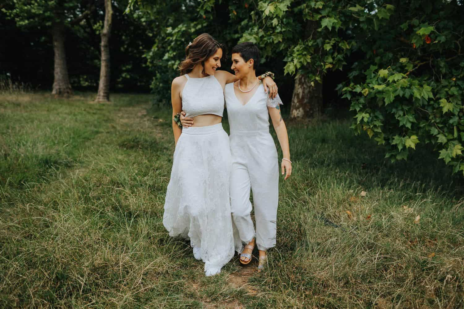 How To Make A Photography Website Your Dream Clients Can't Resist: Two brides walk through the woods with their arms wrapped around each other.