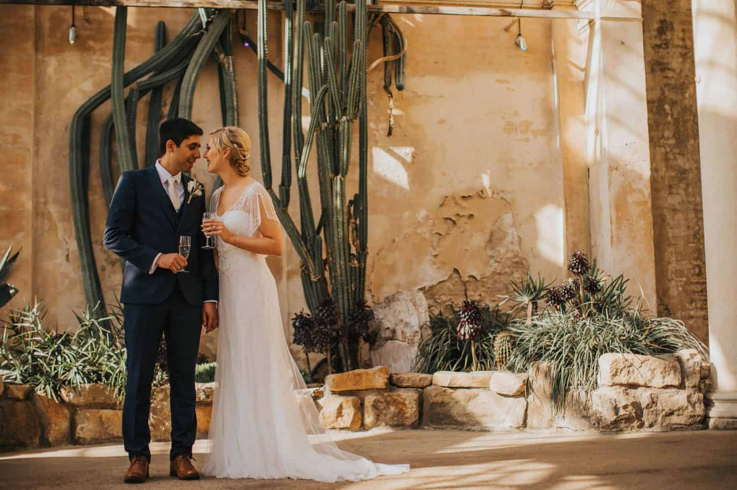 How To Make A Photography Website Your Dream Clients Can't Resist: A bride and groom stand face-to-face, holding champagne in an adobe setting.