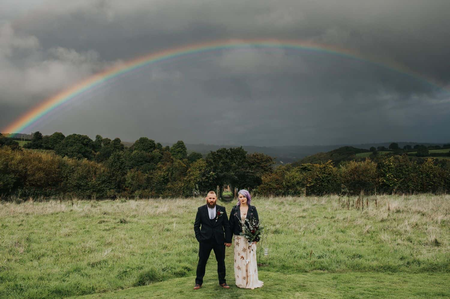 How To Make A Photography Website Your Dream Clients Can't Resist: A punk-rock bride and groom stand in a field below a rainbow glowing through ominous clouds.