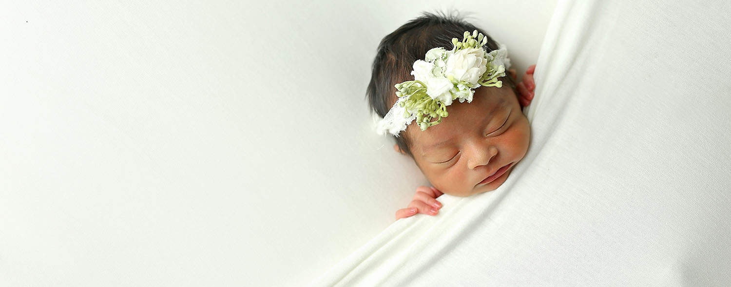 How To Attract New Clients In 3 Bold Business Moves: Newborn baby tucked into a white blanket.