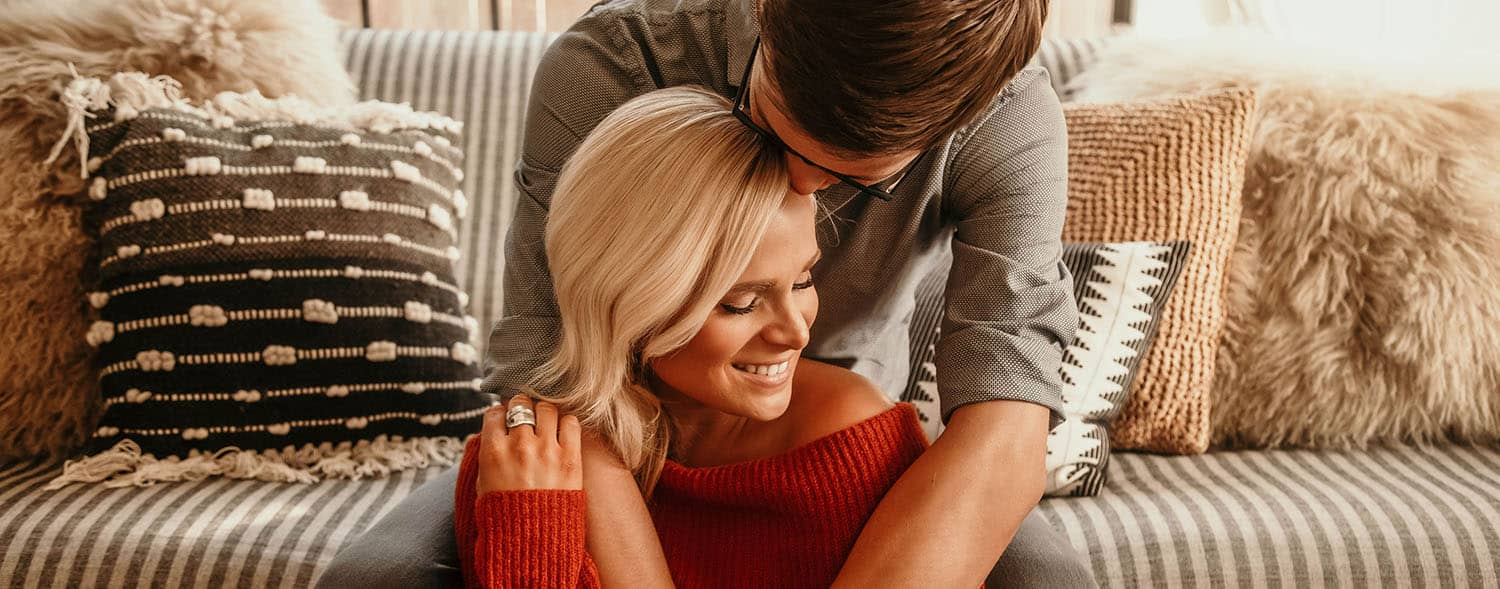 Blonde woman in a red sweater being embraced by a brunette man in a grey shirt.