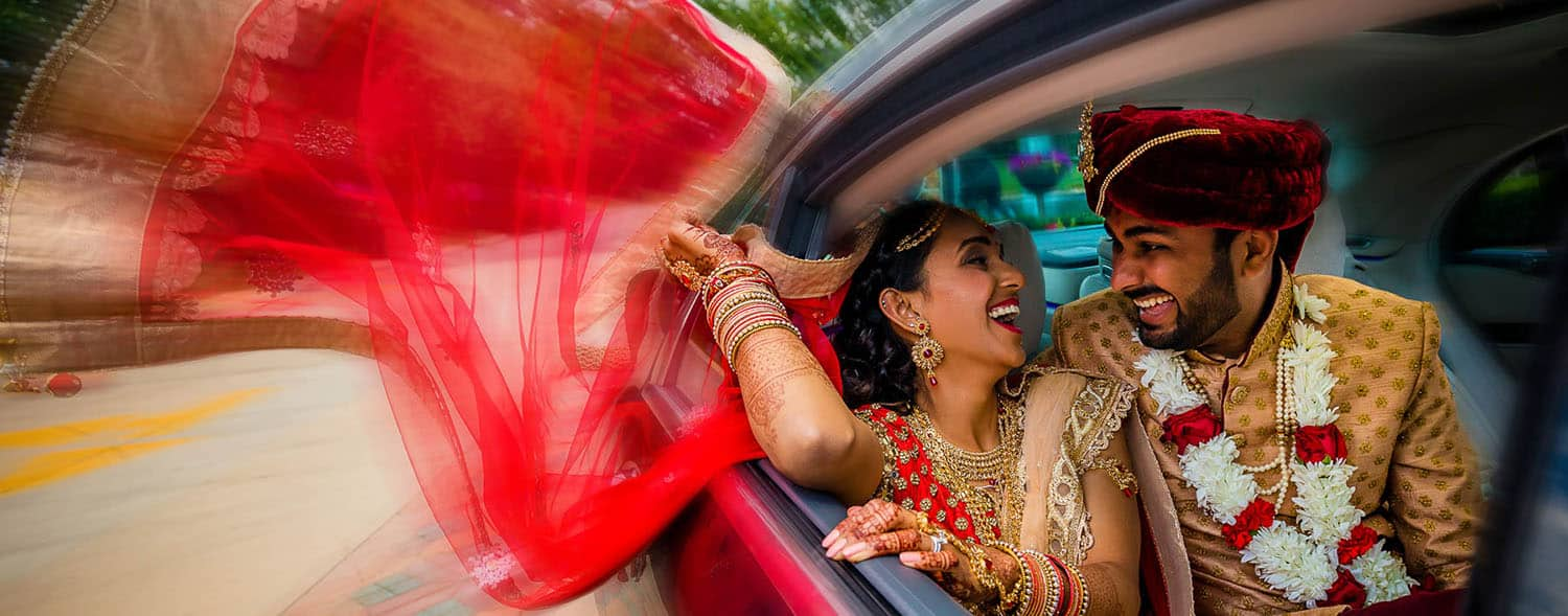 How to Get More Clients: A Wedding Planner Shares Her Secrets (Indian newlyweds laugh in their limo as the bride's veil flows out the window.)