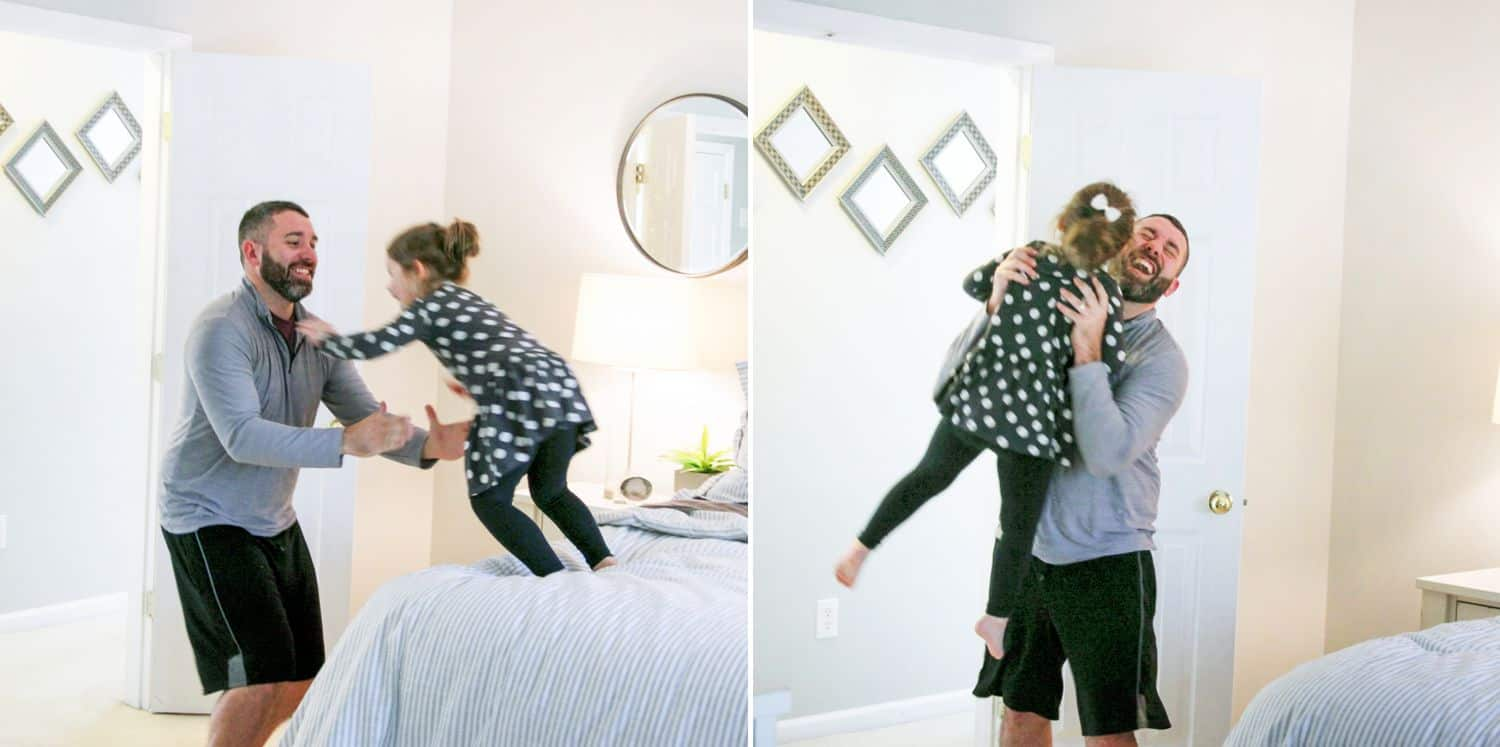 Little girl jumps from the bed into her dad's arms.
