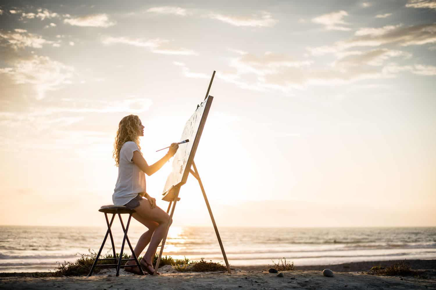 Silhouette of woman painting on the beach.