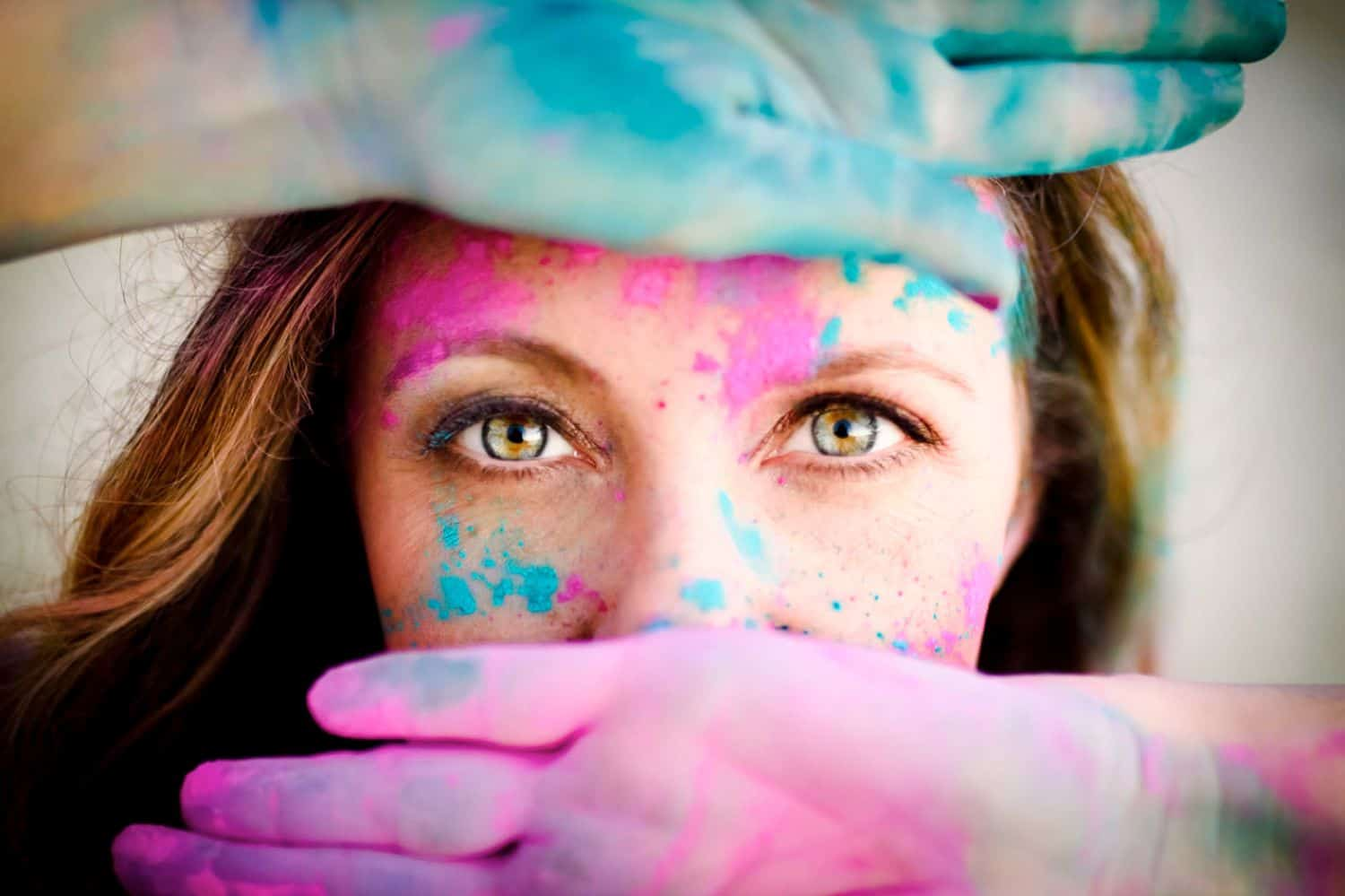 Woman's green eyes framed by paint-covered hands.