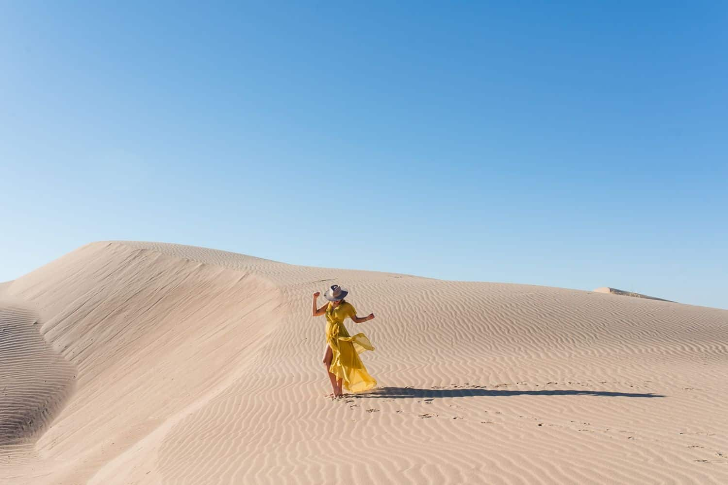 Woman in a yellow dress dancing in the desert.