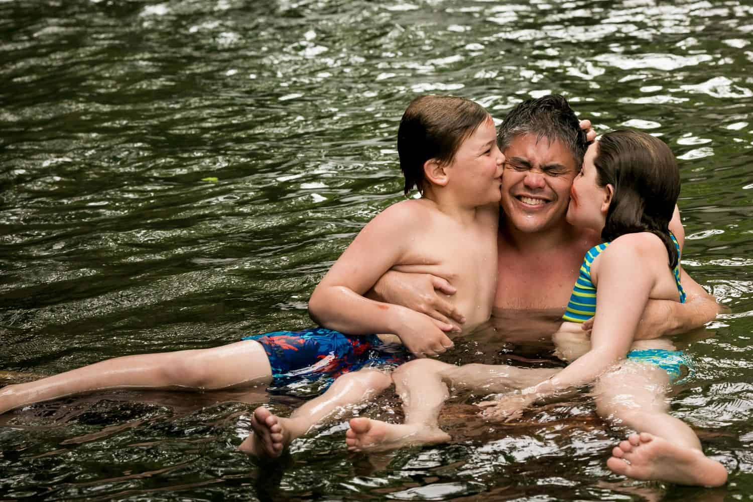 Kids kiss dad on the cheeks as they swim in the lake.