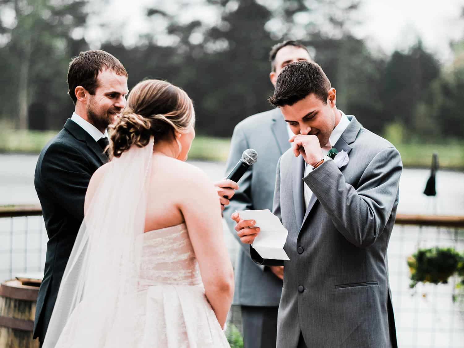 groom cries saying his wedding vows in a lakeside ceremony